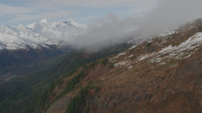 4K stock footage aerial video flying over rocky slopes, under clouds, into mountains, Prince William Sound, Alaska Aerial Stock Footage | AK0001_0421