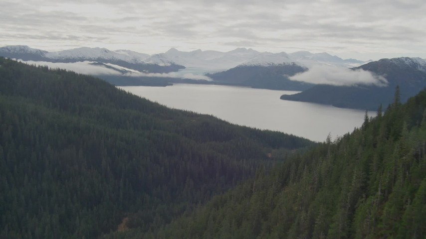 4K stock footage aerial video flying between forested peaks, approaching a bay, Prince William Sound, Alaska Aerial Stock Footage | AK0001_0426
