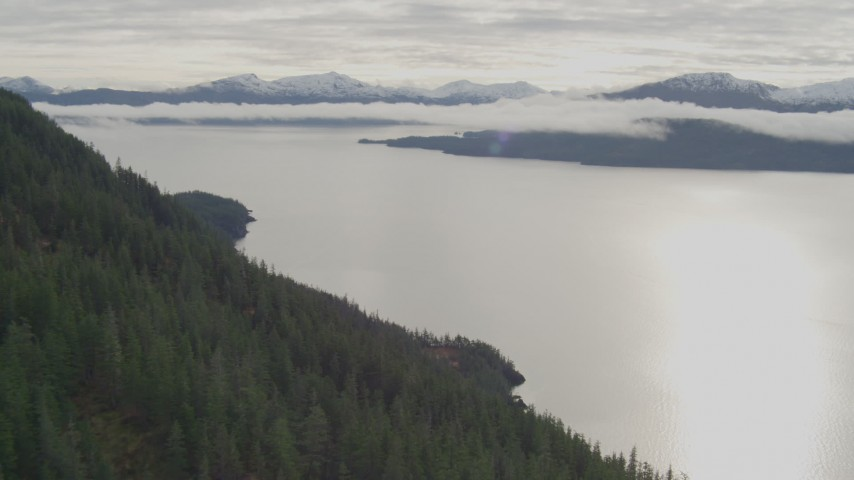 4K stock footage aerial video rounding a forested mountain peak toward a bay, Prince William Sound, Alaska Aerial Stock Footage | AK0001_0427