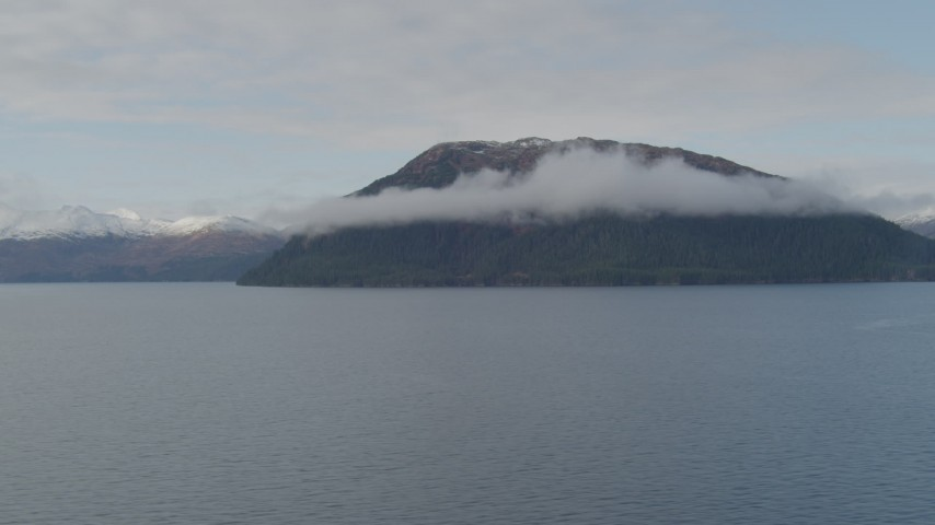 4K stock footage aerial video fly by forested cloud covered peak, from over bay, Prince William Sound, Alaska Aerial Stock Footage | AK0001_0430