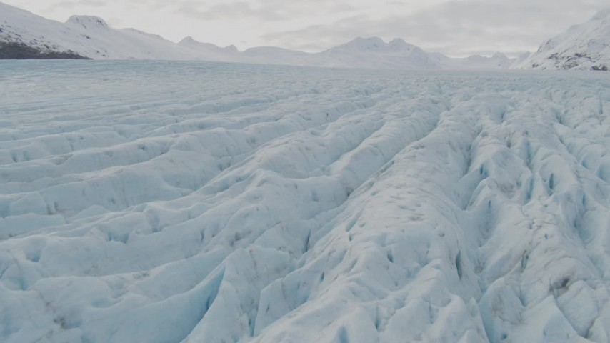 4K stock footage aerial video tilt up from surface of glacier, reveal snowy peaks, Prince William Sound, Alaska Aerial Stock Footage | AK0001_0437
