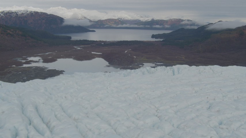 4K stock footage aerial video flying over glacier with a view of the tree lined show, Prince William Sound, Alaska Aerial Stock Footage | AK0001_0451
