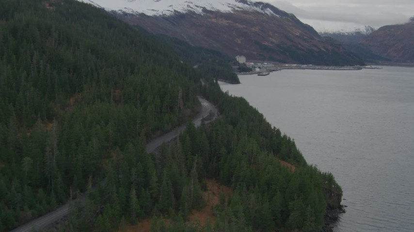 4K stock footage aerial video flying along wooded shoreline and forest road, approaching Whittier, Alaska Aerial Stock Footage | AK0001_0498