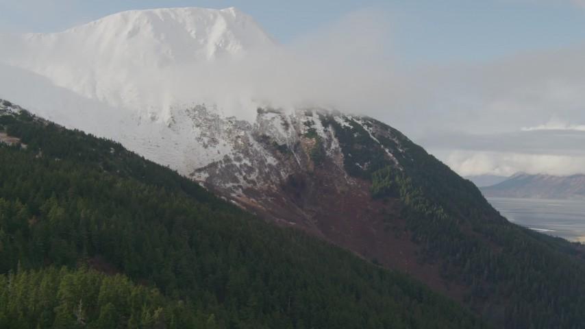4K aerial video flying up wooded slope toward snow capped peak, Kenai Mountains, Alaska Aerial Stock Footage | AK0001_0525