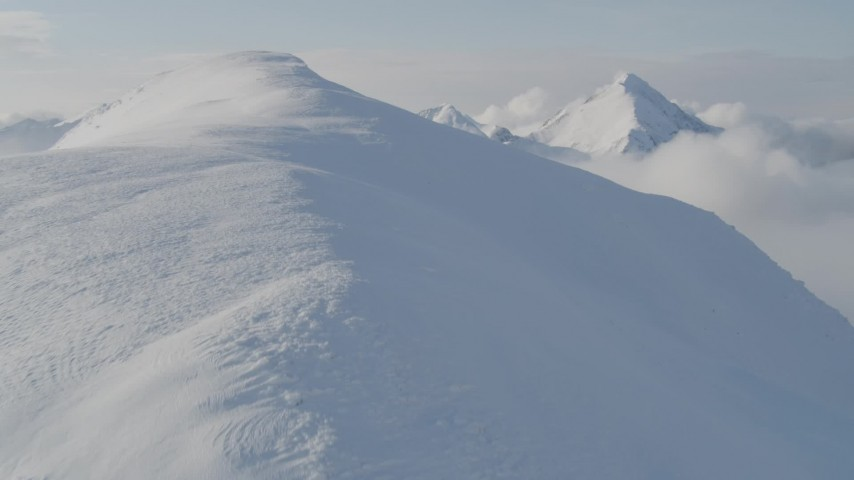 4K aerial video flying through low clouds up the summit of a peak, Kenai Mountains, Alaska Aerial Stock Footage AK0001_0534