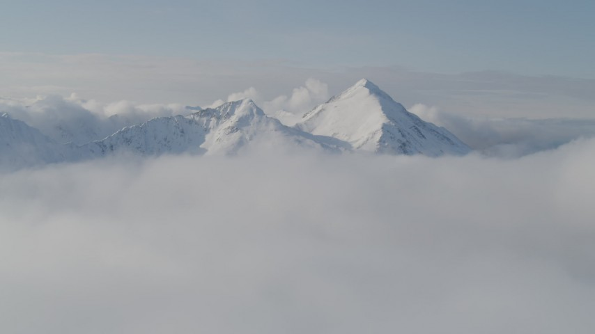 4K stock footage aerial video flying by snow covered Kenai Mountains, low clouds, Kenai Mountains, Alaska Aerial Stock Footage | AK0001_0535