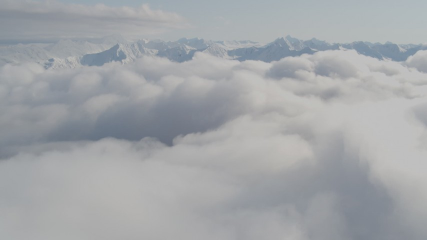 4K stock footage aerial video flying over low clouds, by snow capped peaks, Kenai Mountains, Alaska Aerial Stock Footage | AK0001_0536