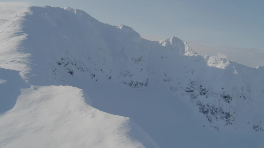 4K aerial video flying by a snowy summit, Kenai Mountains, Alaska Aerial Stock Footage | AK0001_0537