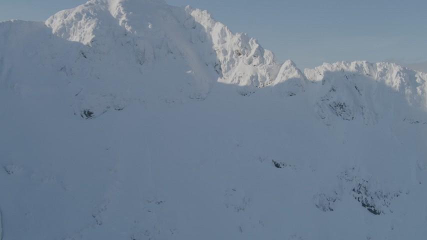 4K stock footage aerial video flying over snowy ridge, revealing mountain peaks, Kenai Mountains, Alaska Aerial Stock Footage | AK0001_0538