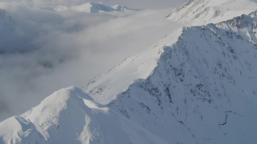 4K stock footage aerial video descending a snowy ridge, approaching low clouds, Kenai Mountains, Alaska Aerial Stock Footage | AK0001_0541