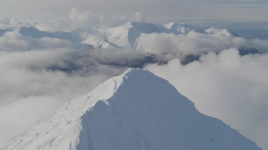 4K stock footage aerial video ascending snowy peak, reveal low clouds, snowy Kenai Mountains, Alaska Aerial Stock Footage | AK0001_0545