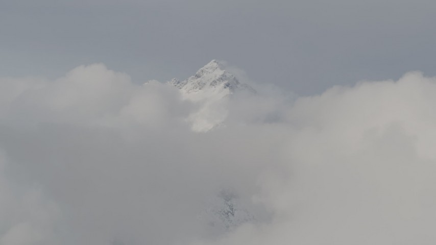 4K stock footage aerial video flying by snowy summit surrounded by low clouds, Chugach Mountains, Alaska Aerial Stock Footage | AK0001_0554