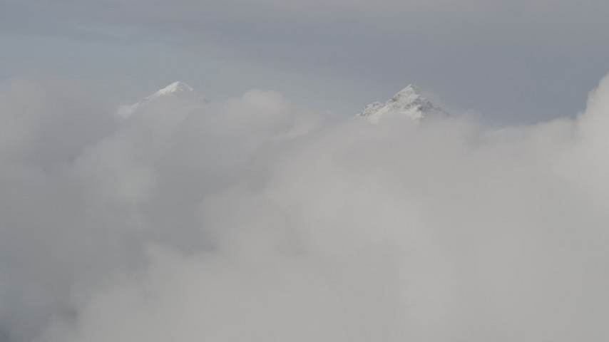4K stock footage aerial video flying over low clouds, approaching snowy summits, Chugach Mountains, Alaska Aerial Stock Footage | AK0001_0556