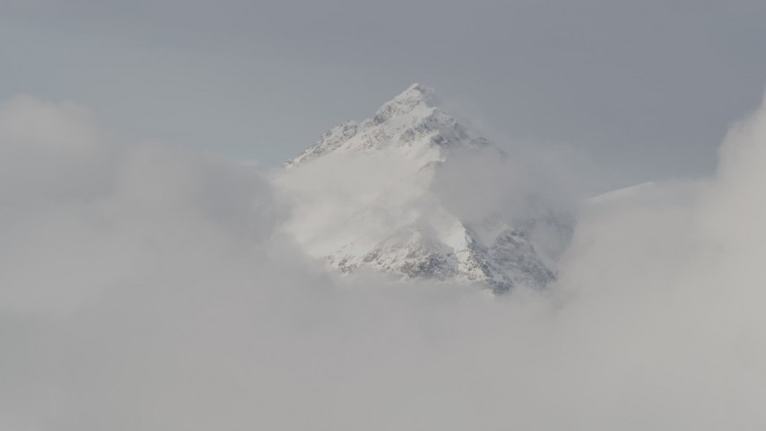 4K stock footage aerial video approaching a snow covered peak, low clouds, Chugach Mountains, Alaska Aerial Stock Footage | AK0001_0557