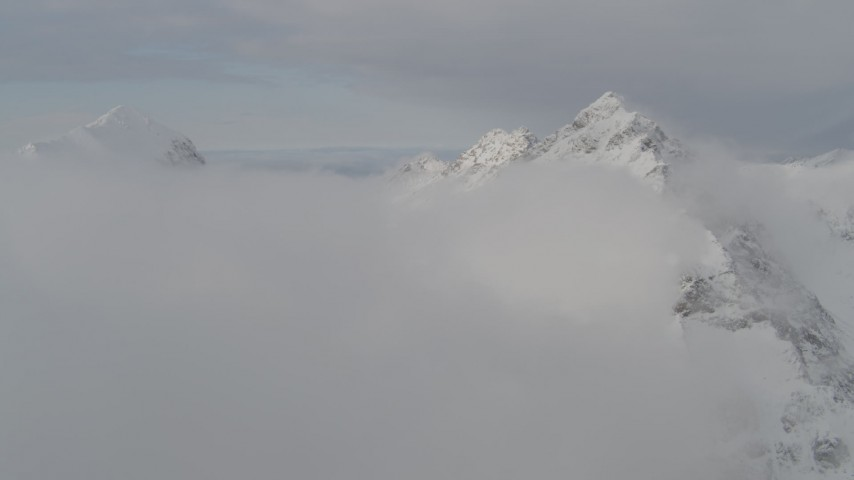 4K stock footage aerial video flying by a snow covered peak, low clouds, Chugach Mountains, Alaska Aerial Stock Footage | AK0001_0561