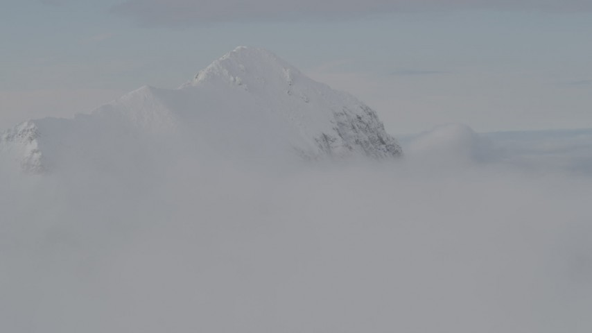 4K stock footage aerial video flying by snow covered peak, surrounded by clouds, Chugach Mountains, Alaska Aerial Stock Footage | AK0001_0562