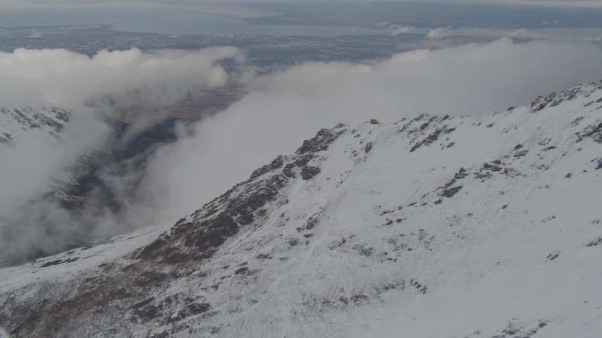 4K stock footage aerial video flying by snow capped mountains, with low clouds, Chugach Mountains, Alaska Aerial Stock Footage | AK0001_0570