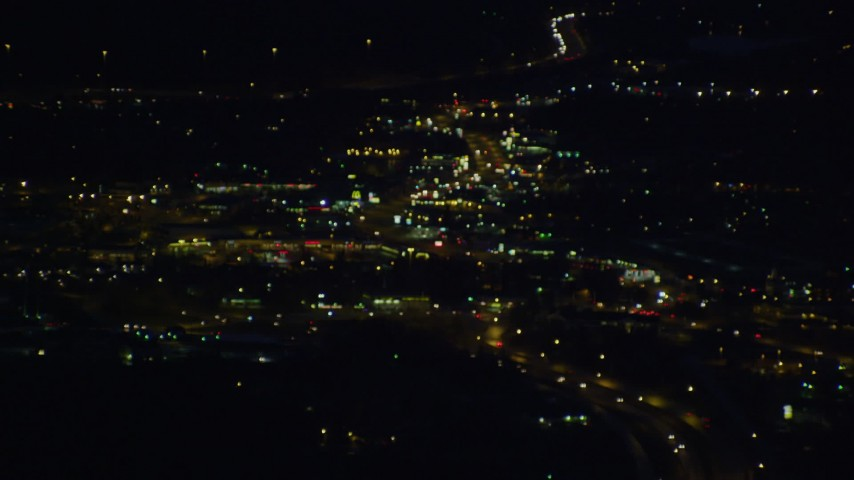 4K stock footage aerial video flying by blurred lights, clearing to reveal city, city roads, Anchorage, Alaska, night Aerial Stock Footage | AK0001_0604