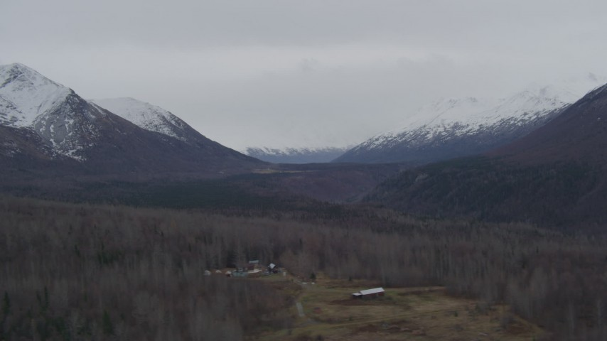 4K stock footage aerial video flying by wooded valley, houses, snow-capped Chugach Mountains, Alaska Aerial Stock Footage | AK0001_0624
