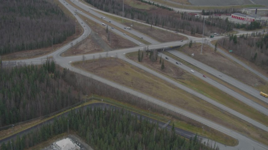4K stock footage aerial video following Glenn Highway, wooded area, by an overpass, Eagle River, Alaska Aerial Stock Footage | AK0001_0665