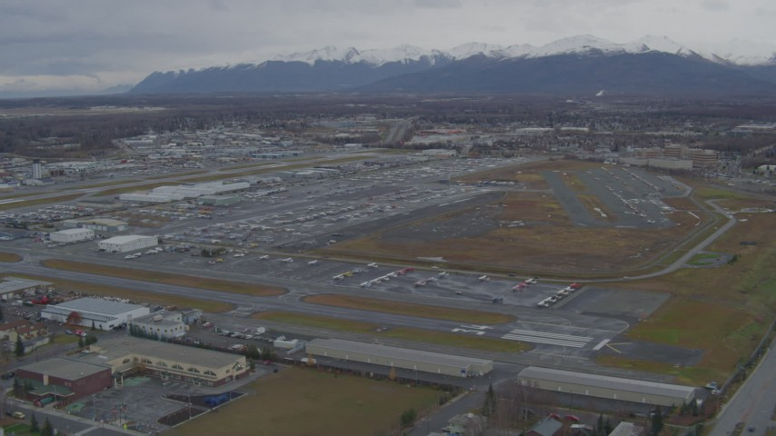 4K stock footage aerial video approaching distant snow-capped mountains, Merrill Field, Anchorage Aerial Stock Footage | AK0001_0691