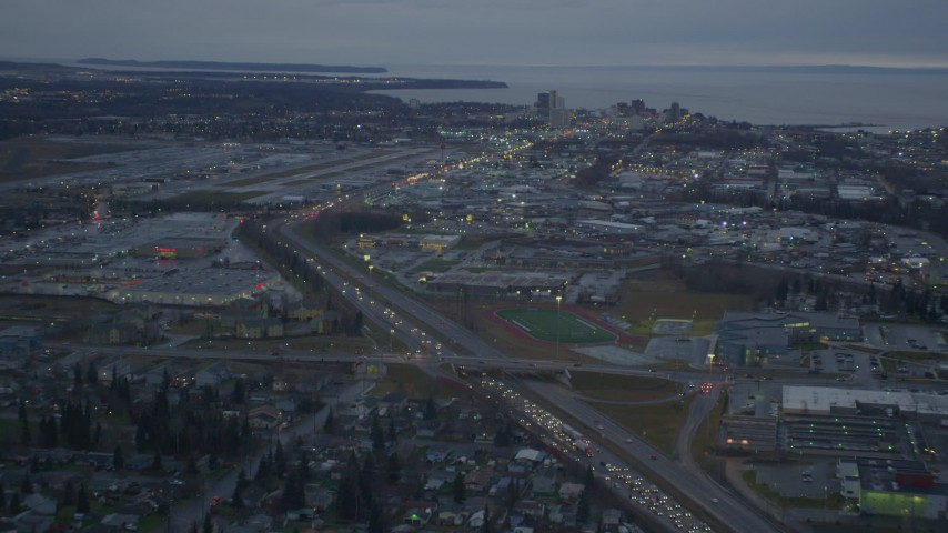 4K stock footage aerial video flying by Glenn Highway, reveal Merrill Field, Downtown Anchorage, Alaska, twilight Aerial Stock Footage | AK0001_0724