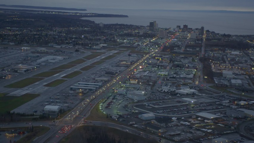4K aerial video flying over large stores by Glenn Highway, revealing Downtown Anchorage, Alaska, twilight Aerial Stock Footage | AK0001_0725