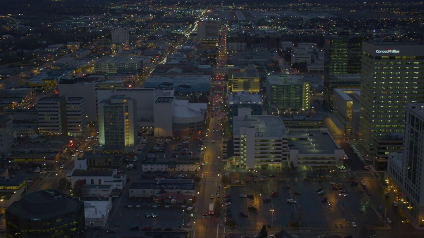 4K stock footage aerial video following West 6th Ave, during winter, through Downtown Anchorage, Alaska, night Aerial Stock Footage | AK0001_0736
