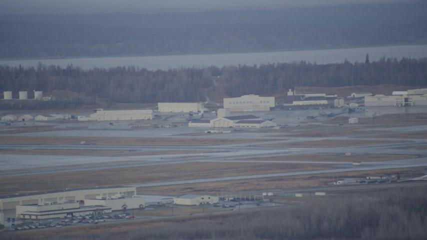 4K stock footage aerial video flying by hangars, runway in winter, Elmendorf Air Force Base, Anchorage Aerial Stock Footage | AK0001_0740