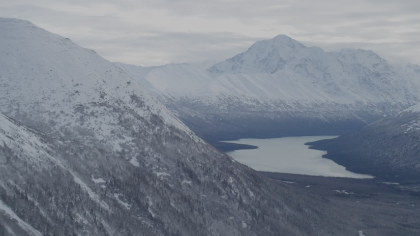 4K stock footage aerial video flying by snow-covered Chugach Mountains bordering Eklutna Lake, Alaska Aerial Stock Footage | AK0001_0776