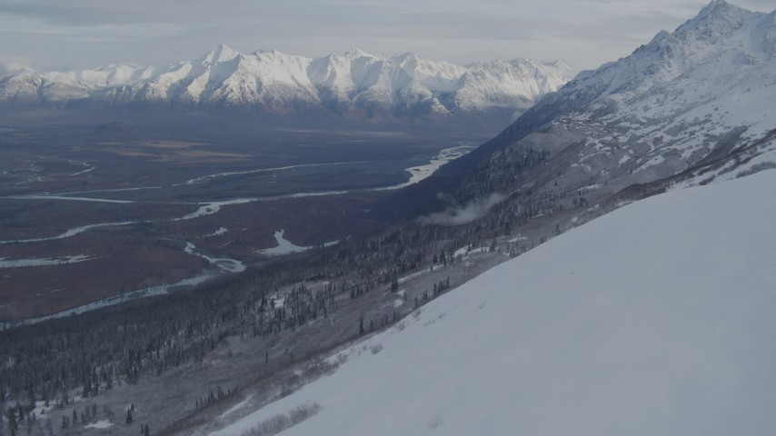 4K stock footage aerial video approaching snowy ridge, revealing a river valley, Chugach Mountains, Alaska Aerial Stock Footage | AK0001_0778