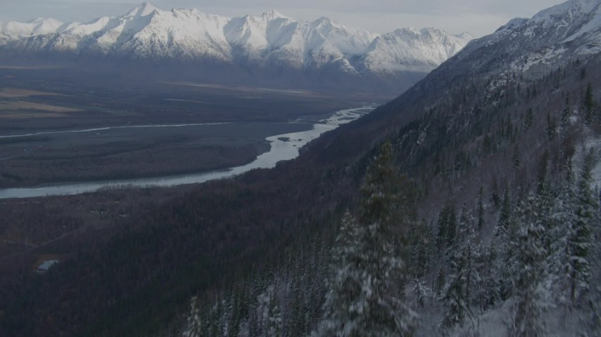 4K stock footage aerial video fly low over treetops, reveal Knik River Valley, snowy Chugach Mountains, Alaska Aerial Stock Footage | AK0001_0783