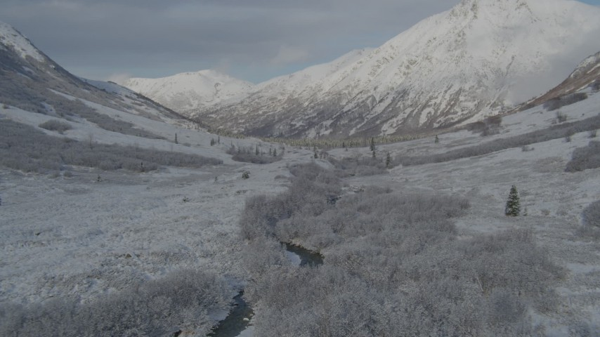 4K stock footage aerial video descending into frosty valley, snow-covered Chugach Mountains, Alaska Aerial Stock Footage | AK0001_0801