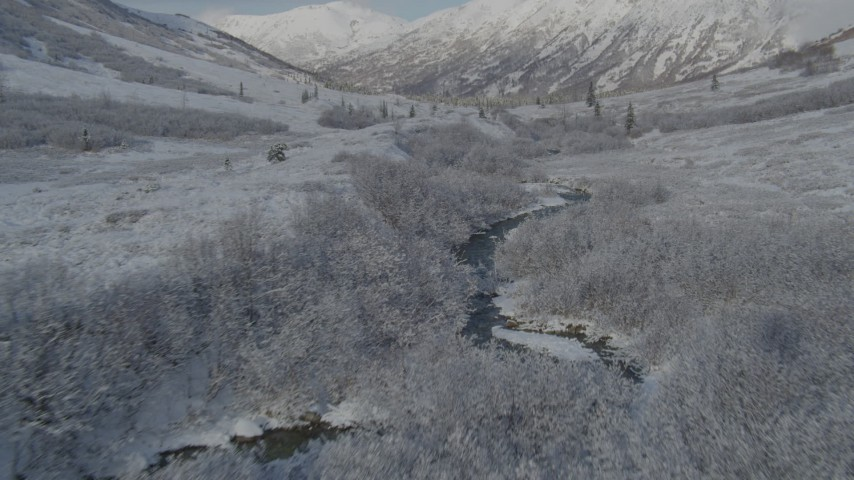 4K stock footage aerial video flying low over river, frosty valley, snow-covered Chugach Mountains, Alaska Aerial Stock Footage | AK0001_0802