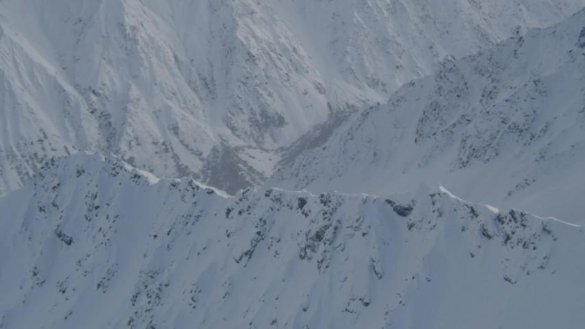 4K stock footage aerial video approaching snowy range, tilt down to slope, Chugach Mountains, Alaska Aerial Stock Footage   AK0001_0840