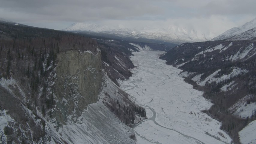 4K stock footage aerial video approaching tree lined cliff over snowy Matanuska River Valley, Alaska Aerial Stock Footage | AK0001_0880