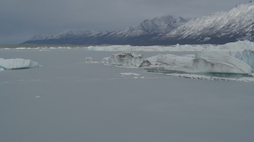 4K stock footage aerial video flying near edge of snow covered glacier, during winter, over Tazlina Lake, Alaska Aerial Stock Footage | AK0001_0943