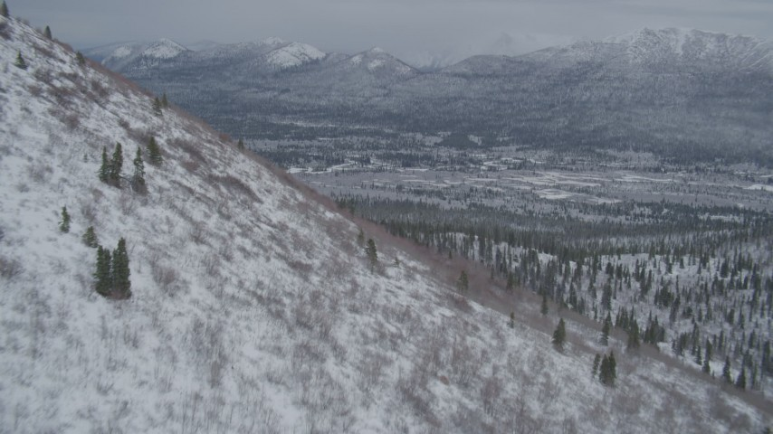 4K stock footage aerial video flying around snowy slope, approaching wooded valley, Chugach Mountains, Alaska Aerial Stock Footage | AK0001_0953