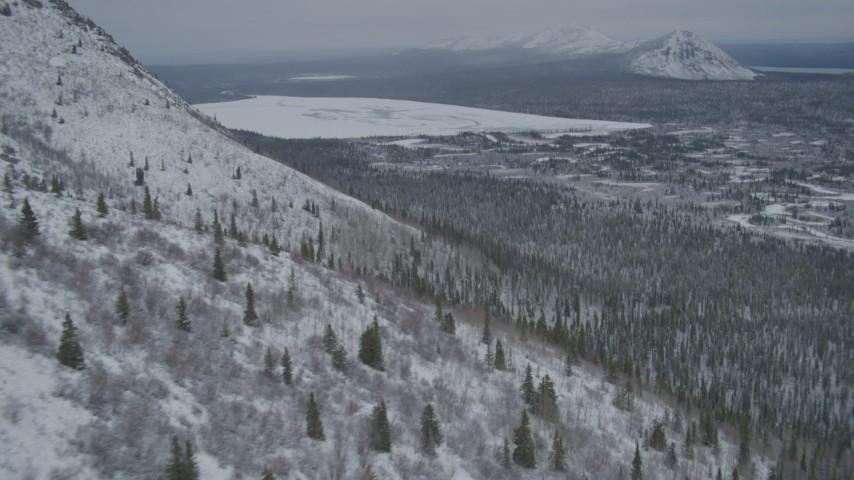 4K stock footage aerial video rounding snow-covered slope, reveal Kaina Lake, Chugach Mountains, Alaska Aerial Stock Footage | AK0001_0954