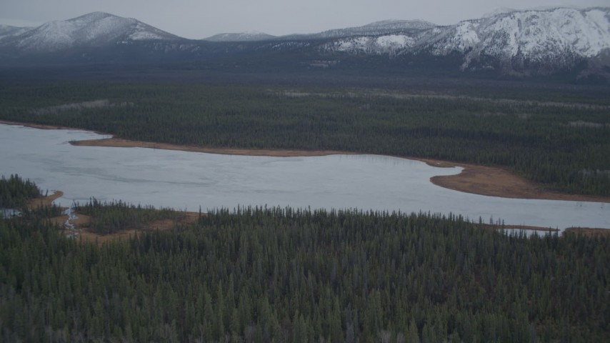 4K stock footage aerial video flying over lake surrounded by forest during winter, Saint Anne Lake, Alaska Aerial Stock Footage | AK0001_0965