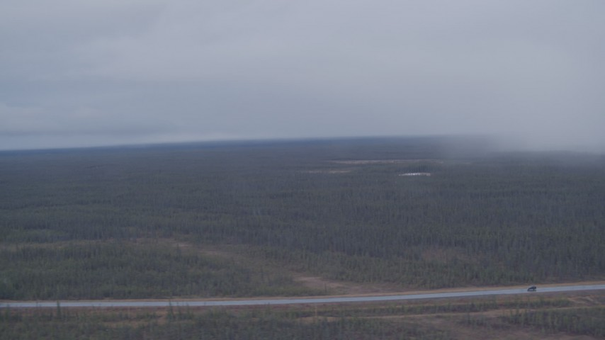 4K stock footage aerial video flying by forest during a rain storm to reveal a highway in the Alaskan Wilderness Aerial Stock Footage | AK0001_1019