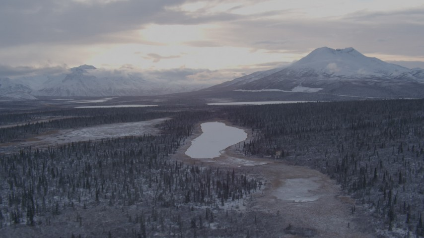 4K aerial video flying over snow covered forest toward Long Lake, Alaska Aerial Stock Footage | AK0001_1053