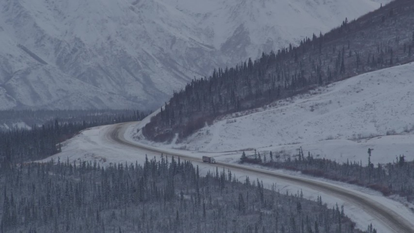 4K aerial video Glenn Highway winding around snowy Talkeetna Mountain, Alaskan Wilderness Aerial Stock Footage AK0001_1055