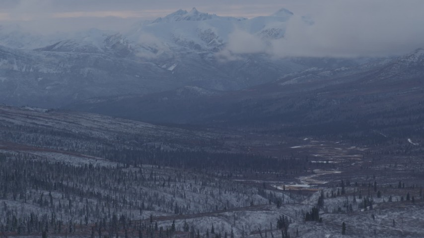 4K stock footage aerial video snow covered, forested hills beneath low clouds, Alaskan Wilderness Aerial Stock Footage   AK0001_1056