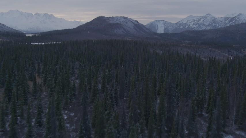 4K stock footage aerial video flying over wooded hills toward snowy peaks, Matanuska River Valley, Alaska Aerial Stock Footage | AK0001_1070