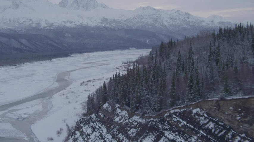4K stock footage aerial video flying over snow covered, tree lined cliffs following Matanuska River, Alaska Aerial Stock Footage | AK0001_1086