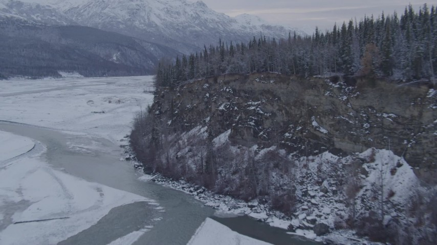 4K stock footage aerial video following the Matanuska River toward snow covered, tree topped cliff, Alaska Aerial Stock Footage | AK0001_1087