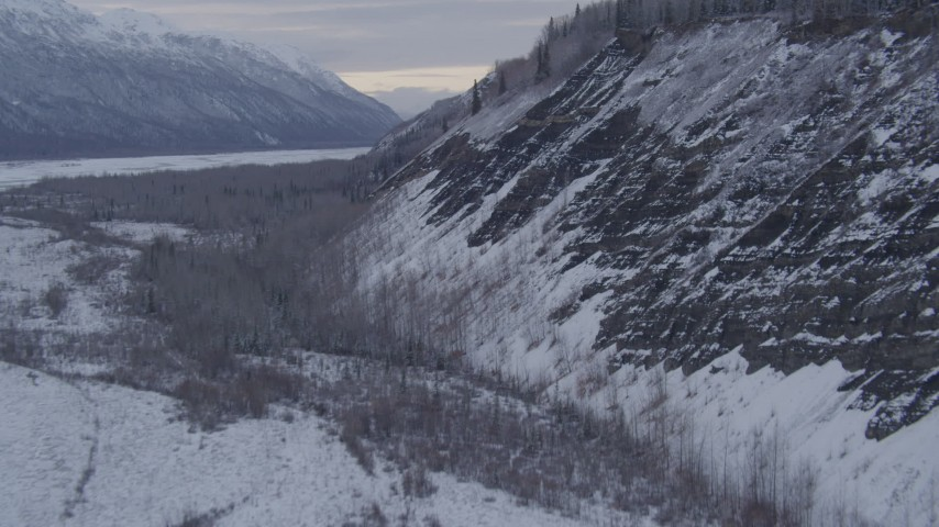 4K stock footage aerial video ascending a snow covered, tree topped cliff, Matanuska River Valley, Alaska Aerial Stock Footage | AK0001_1088