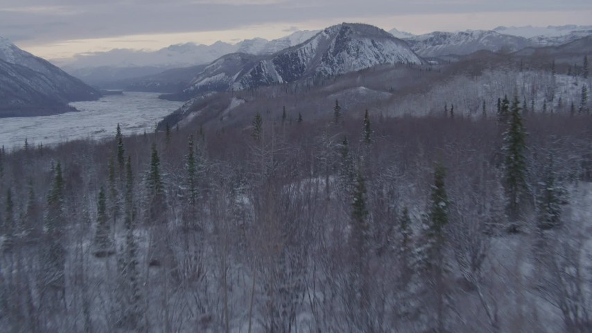 4K stock footage aerial video flying over snow covered, wooded hills toward Matanuska River Valley, Alaska Aerial Stock Footage | AK0001_1090