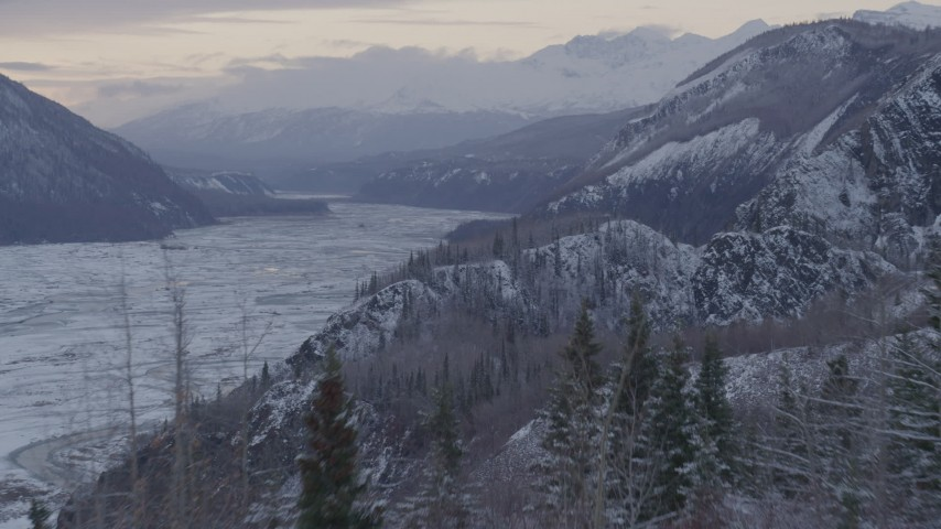 4K stock footage aerial video flying over a snow covered, wooded cliff revealing Matanuska River Valley, Alaska Aerial Stock Footage | AK0001_1092